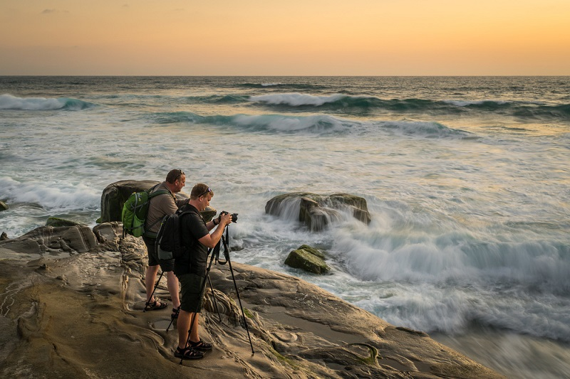 photographers on the beach shooting seascapes with a tripod
