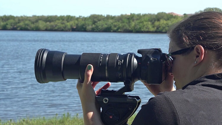 woman shooting nature scenes with a Tamron-150-600