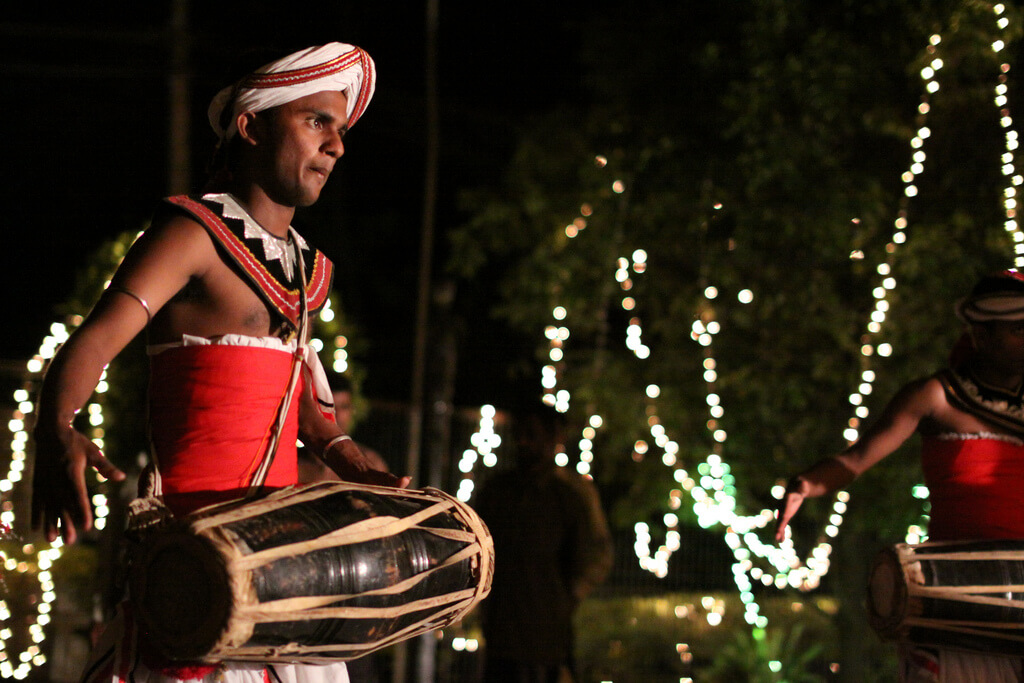 Man photographed while playing a Sri Lankan drum instrument